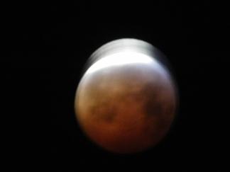 Mondfinsternis Montagmorgen mit viel Lichtverschmutzung als Gegenlicht